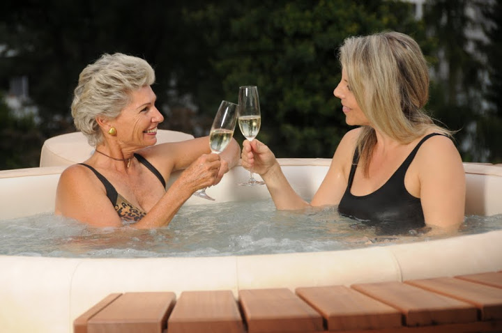 mom and daughter enjoying wine in hot tub