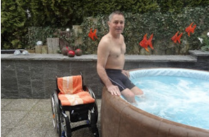 person in wheelchair about to get into hot tub